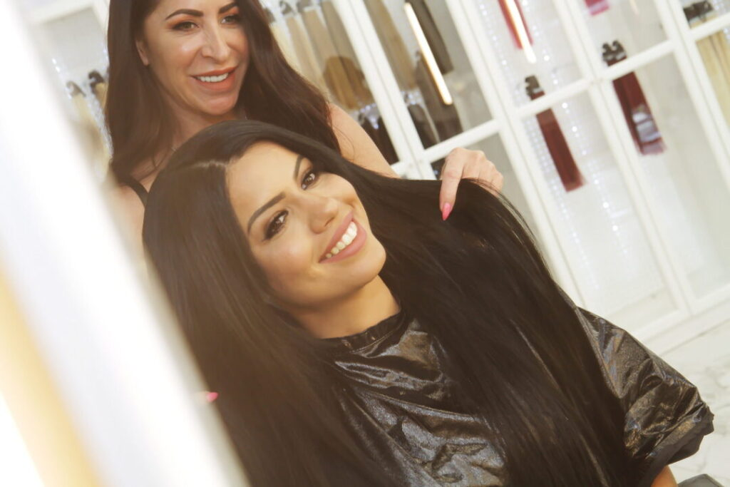 Hair Stylist Showing How To Maintain I-Tip Hair Extensions in Las Vegas at Hottie Hair Salon & Extensions Hair Store Las Vegas